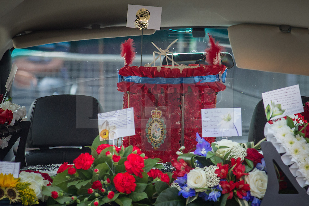 © Licensed to London News Pictures . 12/07/2013 . Bury , UK . A tribute in the shape of a drum is loaded on to the hearse , after the service . The funeral for Fusilier Lee Rigby at Bury Parish Church in Bury town centre today (Friday 12th July 2013) , watched by 100s of people . Fusilier Rigby's coffin was held in Bury Parish Church overnight , watched over by an honour guard of soldiers from the 2nd Battalion Royal Regiment of Fusiliers ( 2RRF ) . Rigby was brutally murdered in Woolwich , London on 22nd May 2013 . Photo credit : Joel Goodman/LNP