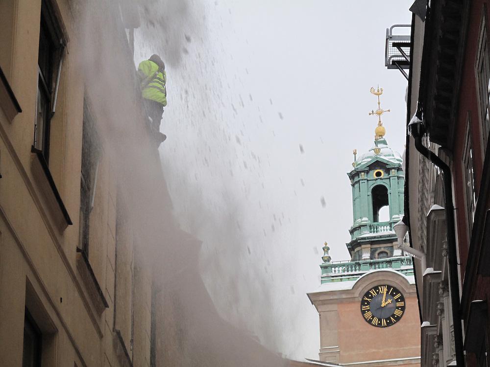 Snöskottning av tak i Gamla stan