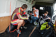 Rijders Wil Baselmans (links) en Sebastiaan Bowier (rechts) schuilen met teamleider Paul Denissen in de bus voor de regen. HPT Delft, een team van studenten van de TU Delft en de VU Amsterdam, trainen op de baan van de RDW voor de recordpoging ligfietsen.<br /> <br /> Riders Wil Baselmans (left) and Sebastiaan Bowier (right) are sheltering in a van for the rain. The HPT (Human Powered Team) is training at the test track in Lelystad for their attempt to break the world record Human Powered Vehicles.