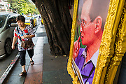 29 DECEMBER 2013 - BANGKOK, THAILAND:   A woman walks past pictures of Bhumibol Adulyadej, the King of Thailand, for sale near Democracy Monument in Bangkok. Thailand is a constitutional monarchy and the King has very limited powers but he is widely revered throughout the country.       PHOTO BY JACK KURTZ