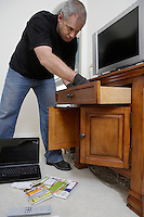 Burglar looking through drawers in house