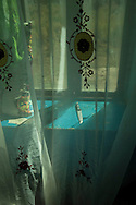 A knife sits in the window sill behind a voile curtain in the home of Zebynisso.