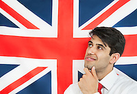 Thoughtful young man with hand on chin against British flag