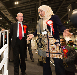© Licensed to London News Pictures. 12/06/2015. London, UK. Labour's JOHN BIGGS leaves the stage with Independent candidate, RABINA KHAN after winning the Tower Hamlets Mayoral election at the Excel Centre in London. Lutfur Rahman was removed from office for fraud and corrupt practices by an election court earlier this year and the 2014 election was rerun as a result. Photo credit : Vickie Flores/LNP