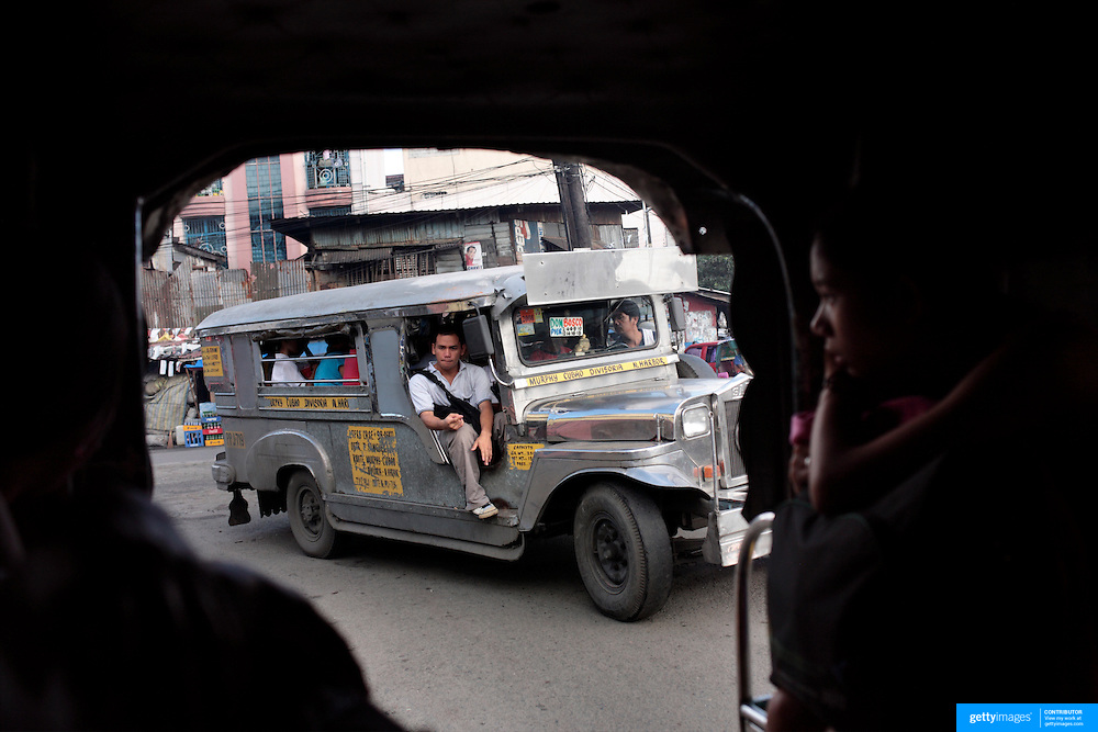 A street view from a Jeepney. Jeepneys are the most popular means of public transport in the Philippines. They were originally made from US military jeeps left over from World War 2 and are well know for their flamboyant decoration and crowded seating. They are a symbol of Philippine culture. on October 8, 2008 at Divasoria markets, Manila, the Philippines. Photo Tim Clayton