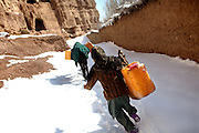 Halemah, 9, is running after her family's donkey on the way to collect water downhill. Halemah lives in the caves with her family since seven years, in Bamyan, central Afghanistan, an area mostly populated by Hazaras. A historically persecuted minority (15%) due to more lenient Islamic faith and characteristic 'Eastern' lineaments, Hazaras constitute the 70% of Bamyan's population.