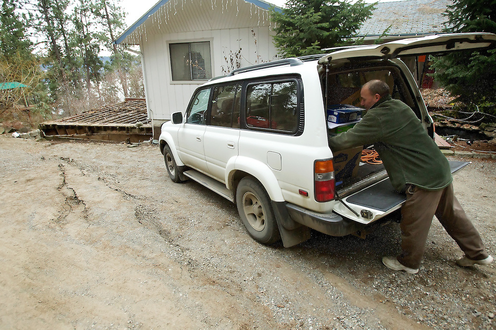 Robert Kobrick loads boxes into his SUV as he retrieves the rest of his belongings from his home Thursday on Regatta Way in Coeur d'Alene. Kootenai County deemed his home unsafe to live in following inspections Tuesday prompted by heavy rains that  caused the soil surrounding his house to shift which caused structural damage to the structure.