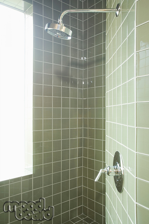 Muted green tiles in shower room