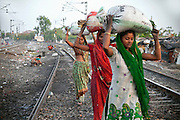 Women are collecting and transporting pieces of coal that have fallen off passing trains along the railway tracks in New Arif Nagar, one of the water-affected colonies standing next to the abandoned Union Carbide (now DOW Chemical) industrial complex, site of the infamous 1984 gas tragedy in Bhopal, Madhya Pradesh, central India. The poisonous cloud that enveloped Bhopal left everlasting consequences that today continue to consume people's lives.