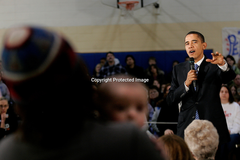 Drew Ostransky (L) holds his son Jasper Larsson (C) as U.S. Democratic presidential candidate Senator Barack Obama (D-IL) answers his question during a campaign stop in Perry, Iowa December 31, 2007. REUTERS/Keith Bedford (UNITED STATES)
