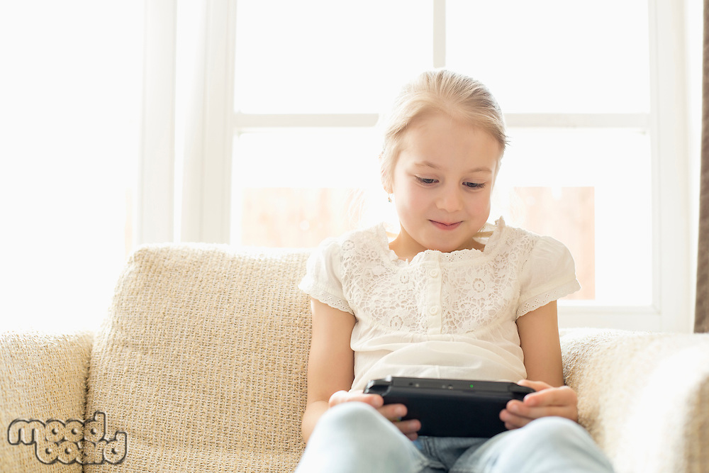 Cute girl playing hand-held video game at home