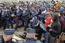 "French police officers go in to stop a fight among a large crowd of migrants as they line-up at a processing centre in ""the jungle"" near Calais, northern France, as the mass exodus from the migrant camp begins."