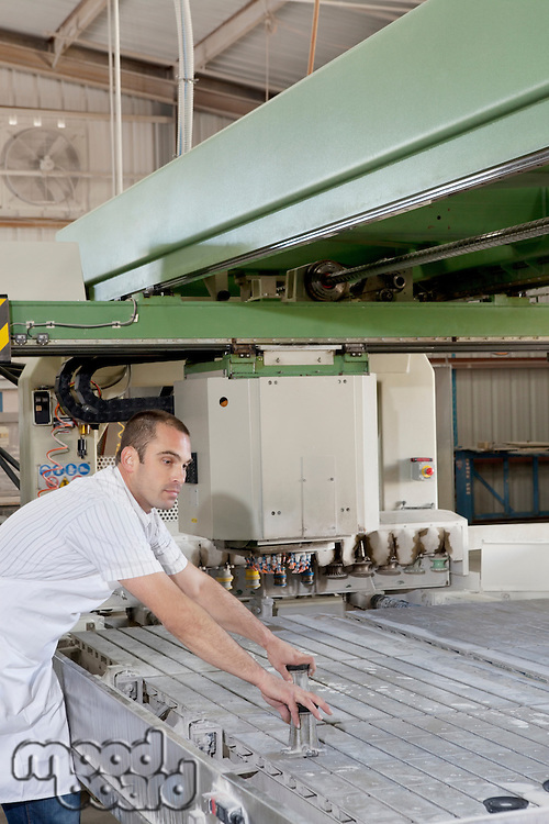Mid adult industrial worker concentrating while operating machinery in factory