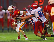 Marion'sTrevor Hardman (16) is brought down by Decorah's Dustin Smith (40) and Michael Peter (82) during the game between the Decorah Vikings and the Marion Indians at Thomas Park in Marion on Friday, August 31, 2012.