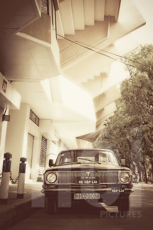 An old car is parked outside Hang Day stadium in Cat Linh street. Hanoi, Vietnam, Asia
