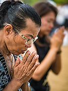 20 OCTOBER 2016 - BANGKOK, THAILAND: A woman in mourning for the late Bhumibol Adulyadej, the King of Thailand, prays on Sanam Luang. Sanam Luang, the Royal Ceremonial Ground, is packed with people mourning the Monarch's death. The King died Oct. 13, 2016. He was 88. His death came after a period of failing health. Bhumibol Adulyadej was born in Cambridge, MA, on 5 December 1927. He was the ninth monarch of Thailand from the Chakri Dynasty and is also known as Rama IX. He became King on June 9, 1946 and served as King of Thailand for 70 years, 126 days. He was, at the time of his death, the world's longest-serving head of state and the longest-reigning monarch in Thai history.        PHOTO BY JACK KURTZ