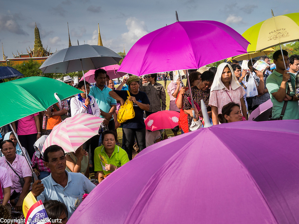 13 MAY 2013 - BANGKOK, THAILAND: People wait for the Royal Ploughing Ceremony to start under umbrellas to shield them from the sun and heat. After the ceremony, thousands of Thais, mostly family formers, rush onto the ploughed ground to gather up the blessed rice seeds sown by the Brahmin priests. The Royal Plowing Ceremony is held Thailand to mark the traditional beginning of the rice-growing season. The date is usually in May, but is determined by court astrologers and varies year to year. During the ceremony, two sacred oxen are hitched to a wooden plough and plough a small field on Sanam Luang (across from the Grand Palace), while rice seed is sown by court Brahmins. After the ploughing, the oxen are offered plates of food, including rice, corn, green beans, sesame, fresh-cut grass, water and rice whisky. Depending on what the oxen eat, court astrologers and Brahmins make a prediction on whether the coming growing season will be bountiful or not. The ceremony is rooted in Brahman belief, and is held to ensure a good harvest. A similar ceremony is held in Cambodia.    PHOTO BY JACK KURTZ