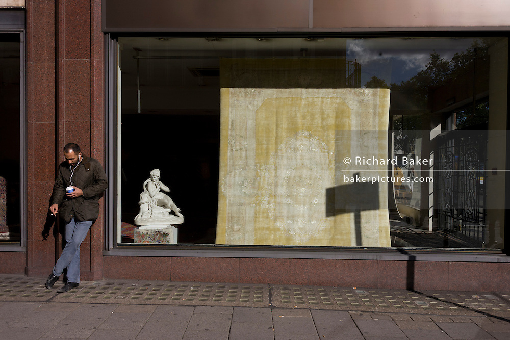 A man takes as break from his job to listen to mp3 music and smoke a quiet cigarette by a carpet and statue shop.