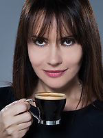 beautiful caucasian brunette drinking coffee on isolated background