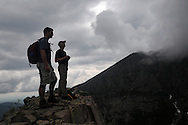 """Jared Leonard, left, and John Walcott watch as clouds roll over the summit of Mt Katahdin in Maine's Baxter State Park from a point that is known as the """"Second Cathedral"""".  The forecast had called for a 30% chance of rain but the mountain is known for creating its own weather.  Walcott and his group were climbing the mountain to celebrate his 60th birthday.  He has been climbing the mountain, which is the highest point in Maine and the northern terminus of the Appalachian Trail, since 1976."""