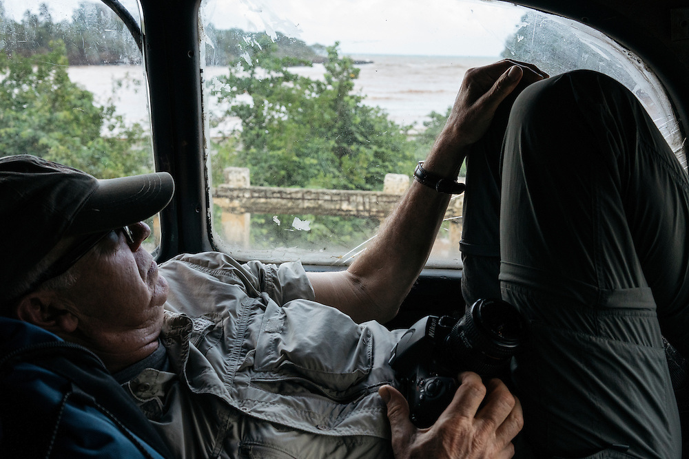 Ornithologist Tim Gallagher lies down in the back of the car while on the road to Taco Bay, a tourist campsite on the coastline, while he and Martjan Lammertink waited for the permit to Humbolt National Park to be accepted on Jan. 26, 2016.
