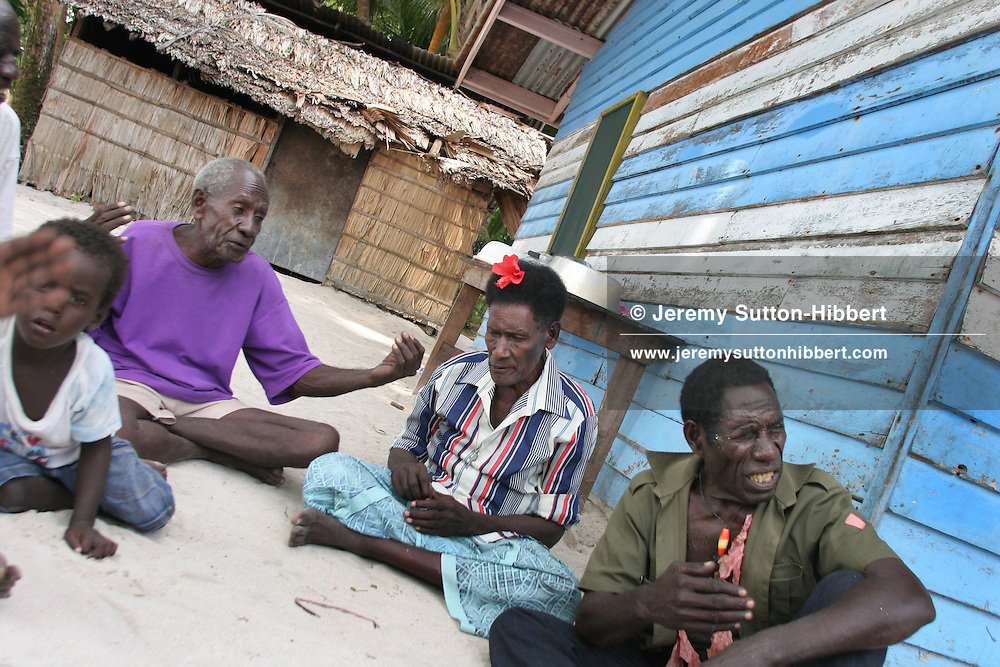 """""""Wise men"""" of the """"council of elders"""" sit discussing traditional prayers and secret ceremonies that they have performed to halt the erosion of their land by the sea, on Han Island, Carterets Atoll, Papua New Guinea, on Monday, Dec. 11, 2006.  Rising sea levels have eroded much of the coastlines of the low lying Carteret islands (situated 80km from Bougainville island, in the South Pacific), and waves have crashed over the islands flooding and destroying what little crop gardens the islanders have. Food is in short supply, banana and swamp taro crops are failing due to the salt contamination of the land, and the islanders live on a meagre one meal per day diet of fish and coconut. There is talk by the Autonomous Region of Bougainville government to relocate the Carteret Islanders to Bougainville island, but this plan is stalled due to a lack of finances, resources, land and coordination."""