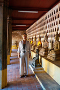 A woman takes in the sights of one of Vientiane's many beautiful temples, Vientiane, Laos.