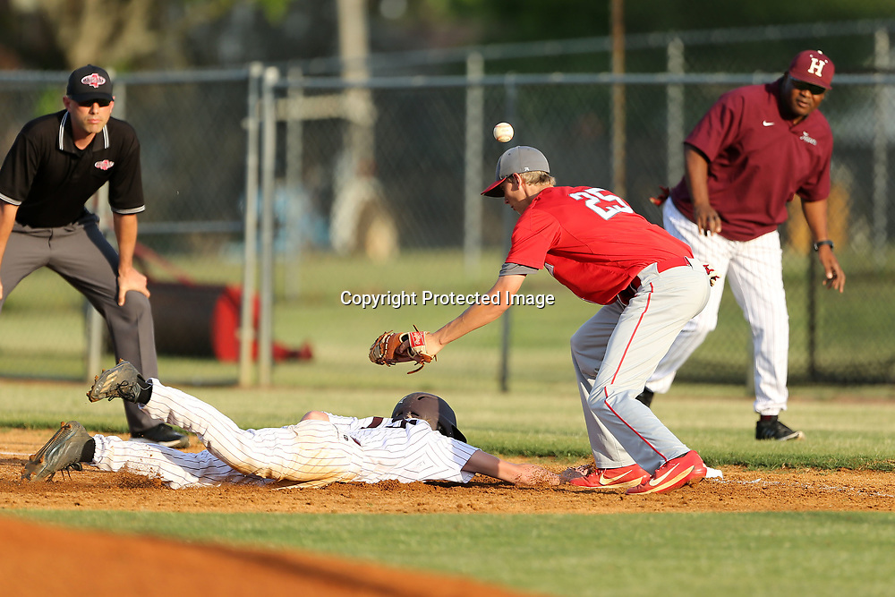 Houston's Colton Peel dives back to first as Lafayette firs baseman Corey Taylor has the ball fly out of his glove in the bottom of the second inning.