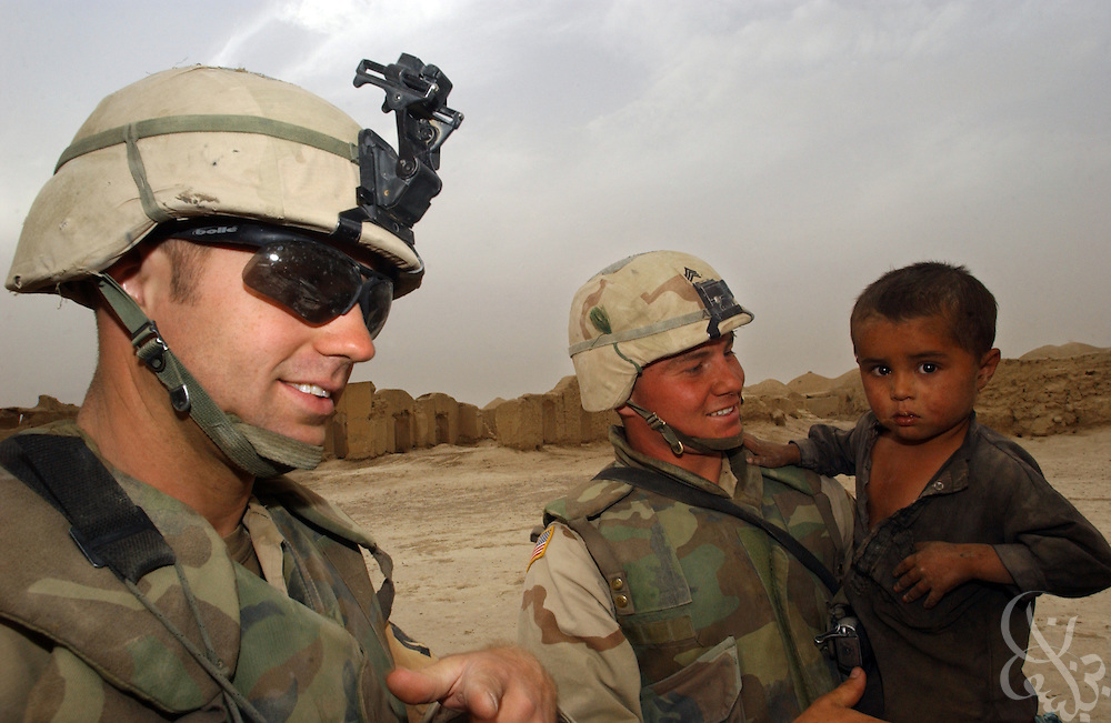 Sgt. Jason Johnson (L) and Sgt. Eric Abelar from the U.S. Army 3rd Platoon 108 MP company play with a local Afghan child while on patrol May 12, 2002 near the Kandahar airfield in southern Afghanistan. U.S. soldiers routinely patrol the area as part of the ongoing coalition Operation Enduring Freedom.