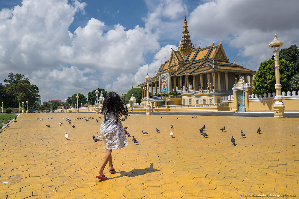 A Cambodian girl chases pigeons in the park in front of the royal palace of Phnom Penh.