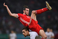 """A player of Uruguay national football team challenges Gareth Bale, top, of Wales national football team in their final match during the 2018 Gree China Cup International Football Championship in Nanning city, south China's Guangxi Zhuang Autonomous Region, 26 March 2018.<br /> <br /> Edinson Cavani's goal in the second half helped Uruguay beat Wales to claim the title of the second edition of China Cup International Football Championship here on Monday (26 March 2018). """"It was a tough match. I'm very satisfied with the result and I think that we can even get better if we didn't suffer from jet lag or injuries. I think the result was very satisfactory,"""" said Uruguay coach Oscar Tabarez. Wales were buoyed by a 6-0 victory over China while Uruguay were fresh from a 2-0 win over the Czech Republic. Uruguay almost took a dream start just 3 minutes into the game as Luis Suarez's shot on Nahitan Nandez cross smacked the upright. Uruguay were dealt a blow on 8 minutes when Jose Gimenez was injured in a challenge and was replaced by Sebastian Coates. Inter Milan's midfielder Matias Vecino of Uruguay also fired at the edge of box from a looped pass but only saw his attempt whistle past the post. Suarez squandered a golden opportunity on 32 minutes when Ashley Williams's wayward backpass sent him clear, but the Barca hitman rattled the woodwork again with goalkeeper Wayne Hennessey well beaten."""