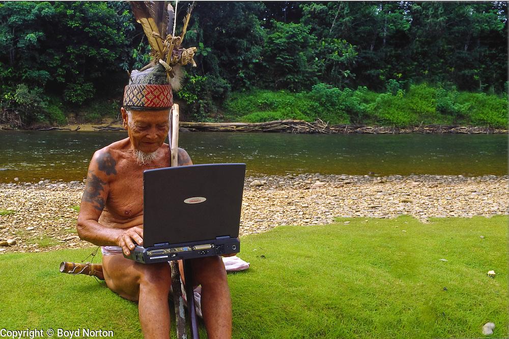Even headhunters have to keep ahead. Iban elder and laptop, Iban tribe, former headhunters, rainforest Skrang River, Sarawak, Borneo, Malaysia.