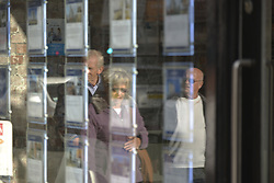 October 19, 2016 - Manchester, England, United Kingdom - A pane of glass reflects light as people pass an estate agent on October 19, 2016 in Manchester, England. The United Kingdom's finance industry regulator, the Financial Conduct Authority, has announced a commitment to consult on mortgage payment shortfall remediation guidance. (Credit Image: © Jonathan Nicholson/NurPhoto via ZUMA Press)