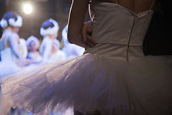 A ballerina watches from the wings before going on stage during a Vietnam National Opera & Ballet performance of Swan Lake at the Hanoi Opera House, Vietnam, Southeast Asia