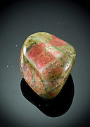 Cutout of an unakite gemstone on black background