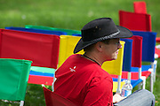 Person in red and black hat, sitting in a sea of colourful outdoor chairs.