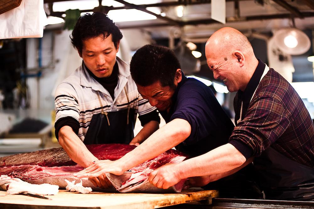 Cutting fresh tuna with a very large blade. Tsukiji Fish Market, Tokyo, Japan