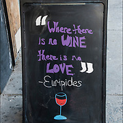Blackboard humorous  outdoor wine store sign. <br /> <br /> Quote: &quot; Where there is no Wine there is no Love&quot; Euripides<br /> <br /> @Taste Wine Co.