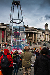 Trafalgar Square, London, Friday 7 November. The Royal British Legion unveiled the Every Man Remembered sculpture in Trafalgar Square, a collaborative piece with the artist Mark Humphrey. The brass sculpture, loosely based on the Unknown Solider, stands on a plinth of limestone sourced from the Somme and is encased in a Perspex obelisk, surrounded by poppies which float up around the figure every five minutes. PICTURED: Tourists addmire the moving, temporary addition to Trafalgar Square.