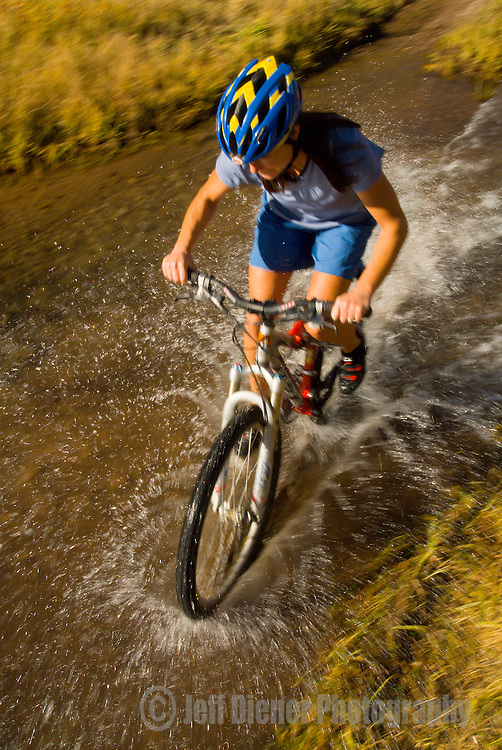 A young woman rides a mountain bike through a stream in Jackson Hole, Wyoming.