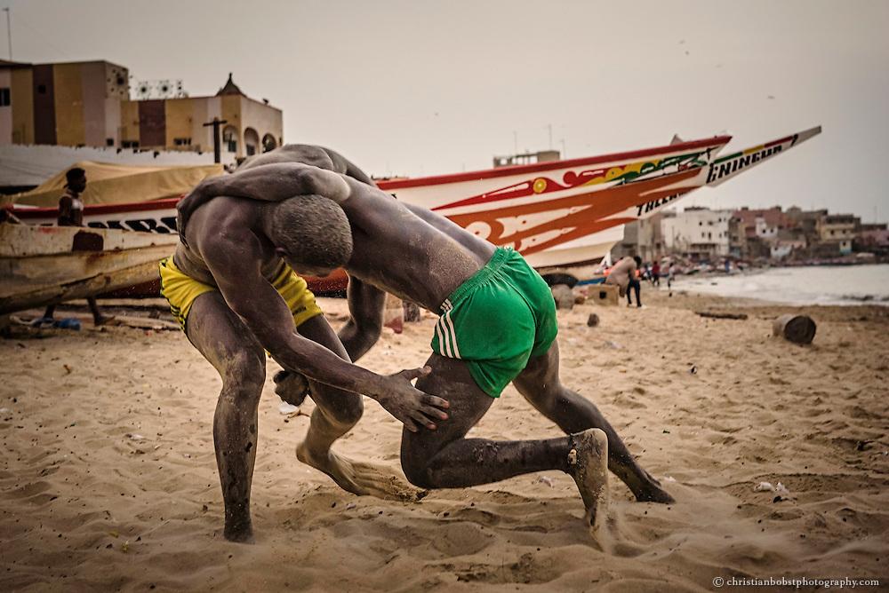 Zwei Ringer trainieren am Strand von Ngor, einem Stadtteil von Dakar, vor traditionellen senegalesischen Fischerbooten. Wie die grossen Champions Bombardier und Yekini  waren viele Ringer ursprünglich Fischer, da das Einziehen der grossen Netze vor der sehr fischreichen senegalesischen Küste sehr viel Kraft und Ausdauer erfordert und die Fischer durch ihre Tätigkeit sehr gut trainiert sind.