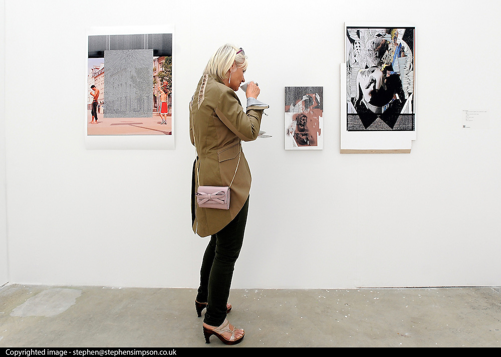 © licensed to London News Pictures. LONDON, UK.  22/06/11. A woman drinks coffee whilst looking at work by Holly Antrum. Students present their work at The Royal College of Art's Fine Art Graduate Show 2011. The show runs from 24th June-3rd July 2011. Mandatory Credit Stephen Simpson/LNP
