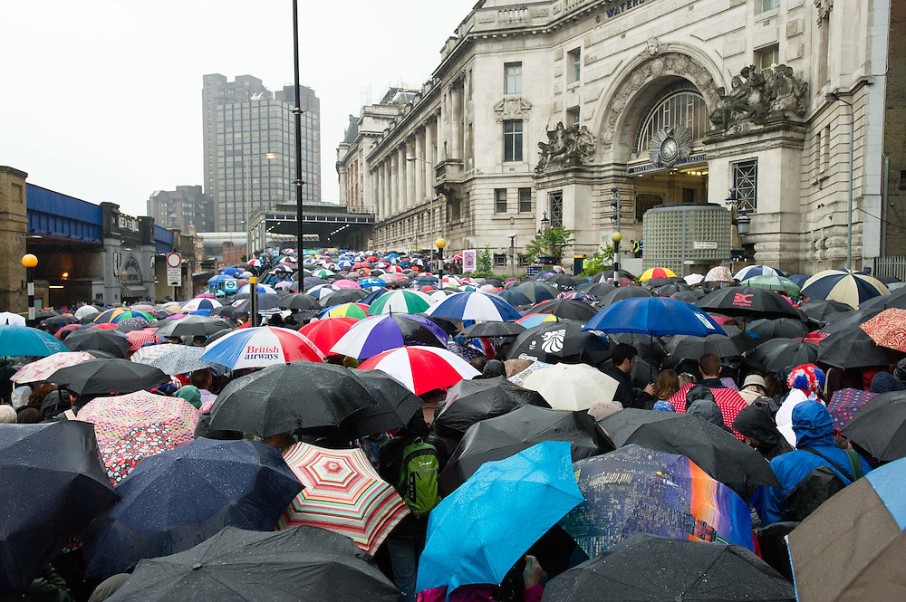 People queuing to get into Waterloo Railway station during a rain storm.