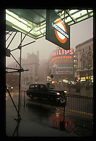 Black cab under heavy rain in Piccadilly Circus, London.