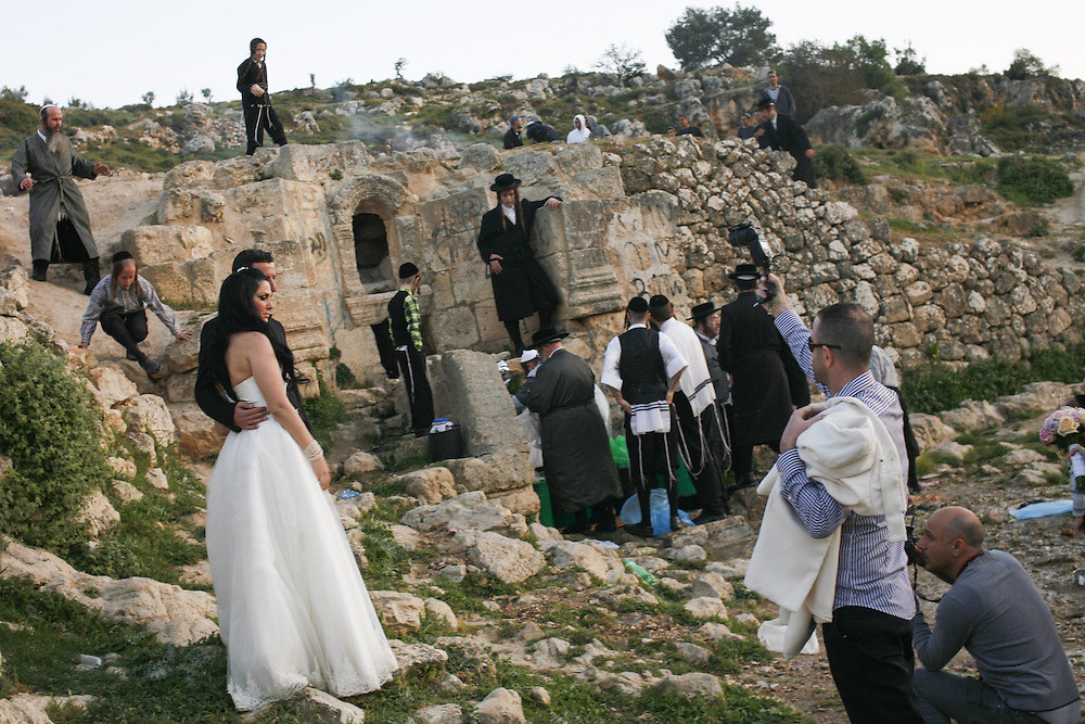 Bride and groom take wedding pictures while Ultra-Orthodox Jews collect water from a mountain spring near Jerusalem on March 24, 2013 to be used in baking the unleavened bread, known as matzoth, during the Maim Shelanu (Rested Water) ceremony.