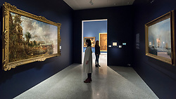 """© Licensed to London News Pictures. 11/01/2019. LONDON, UK. Staff members view """"The Opening of Waterloo Bridge ('Whitehall Stairs, June 18th, 1817')"""" by John Constable (L) and """"Helvoetsluys"""", 1832, by J.M.W. Turner (R) which are exhibited at The Royal Academy of Arts in Piccadilly for the first time since the artists clashed at the Summer Exhibition in 1832.  Turner allegedly added a small dab of red paint to his canvas, which he then converted into an image of a buoy floating in the sea. when he saw his painting next to Constable's.  The two works form """"He has been here and fired a gun"""": Turner, Constable and the Royal Academy, on display from 12 January to 31 March 2019.  Photo credit: Stephen Chung/LNP"""
