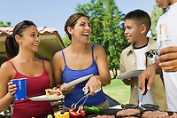 Boy (13-15) with family gathered around grill at picnic.