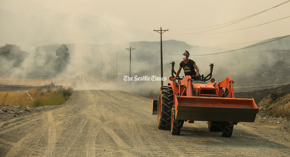 A resident with a tractor comes out to help put out the fire spreading from her neighbor's property on Soren Peterson Road at Johnson Creek Road, northwest of Omak, as wildfires burn central Washington August 20, 2015.<br />