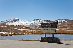 Independence Pass, Colorado:  Top of Independence Pass.  Snow on the ground and skim ice on the pond in mid-September. State Highway 82 skirts some of Colorado's famous 14-ers, mountains more than 14,000 feet high as it crests the Continental Divide at 12,095 feet above sea level.  Open only in high summer, it runs between Twin Lakes and Aspen and is part of Colorado's Top of the Rockies Scenic Byway..