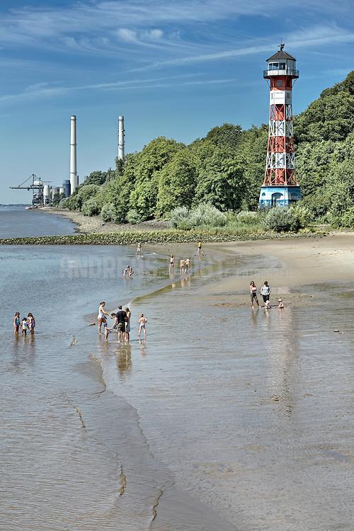 Leute am Strand und im Wasser der Elbe beim Leuchtturm Wittenbergen am Rissener Ufer. Im Hintergrund ist das Kohlekraftwerk Wedel zu sehen.